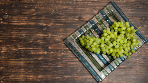 Bunch of grapes lying on a plate, top view Footage