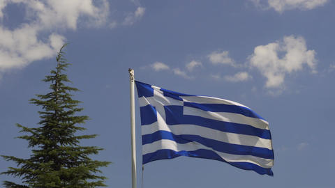 Greek flag waving before blue sky background on a sunny day GIF