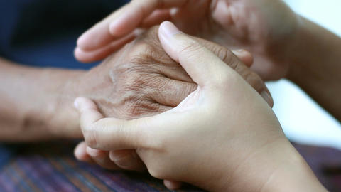 Hands of young woman holding and gentle touch to Hands of old women metaphor and Footage