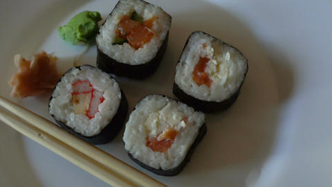 Japanese sushi rolls variety close up rotating on a white dish Archivo