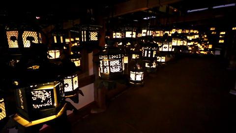 Flickering lanterns hang in a dark room inside Kasuga Taisha, Nara, Japan Image