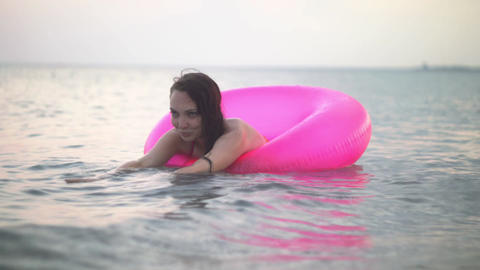 A girl bathes in the evening on an inflatable circle Footage
