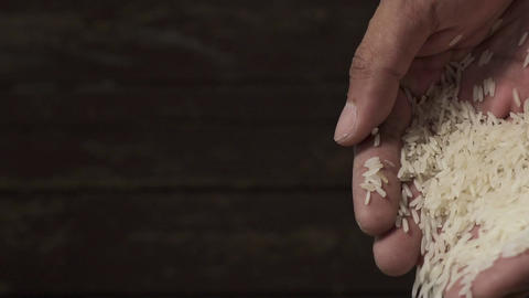 White raw rice grains are falling from a man's hand in slow motion Archivo
