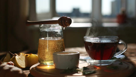 Closeup is authentic honey slowly drains from a spoon. Morning time. Tea Archivo