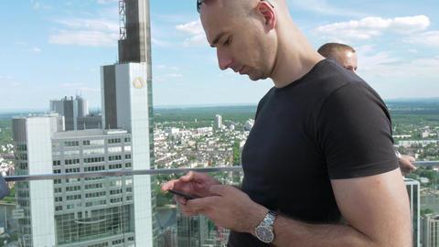 Young man operating smartphone from skyscraper roof Footage