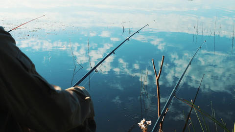 Fishing rod in the hands of a fisherman. Lake Shore. Smooth calm and calm water Footage