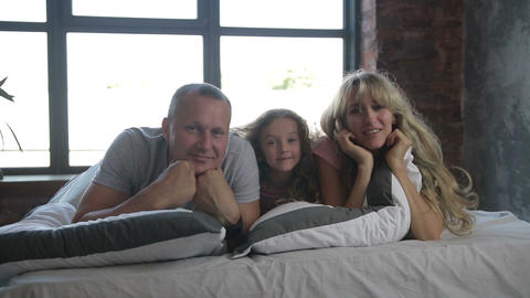 Portrait of family with daughter posing in bed Archivo