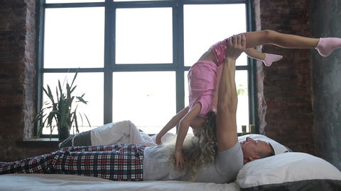 Joyful dad lifting cute curly daughter up in bed Image