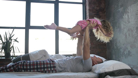 Happy father letting his daughter fly in bedroom Footage
