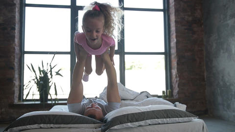 Playful father lifting his daughter on bed at home Footage
