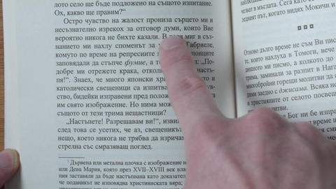 Reading a book close up, finger pointing the text Footage