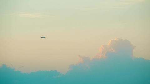 Distant commercial airplane flying against beautiful sunset clouds Footage