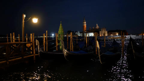 Moored gondolas in Venice at night and distant San Giorgio Maggiore island Footage