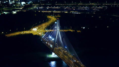 Aerial night shot of the modern guyed bridge over the Vistula river in Warsaw Footage