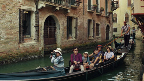 VENICE, ITALY - AUGUST 8, 2017. Asian family taking a ride on a famous Venetian Footage