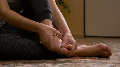 Closeup of barefoot young woman massaging her sprained foot having painful Footage