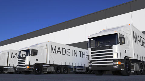 Freight semi trucks with MADE IN THE UK caption on the trailer loading or Live Action