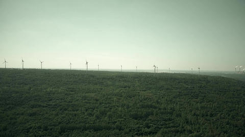 Windmills and distant smoking stacks of a traditional power plant Footage