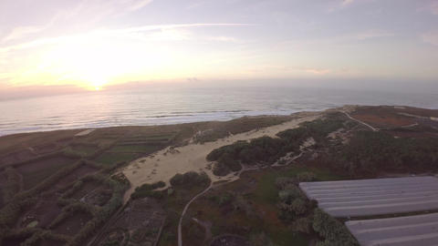 Aerial view over ocean grass sand dunes at sunrise with ocean in the background  Footage