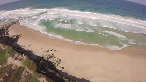 Aerial view of ocean waves along a beach and cliffside - Portugal Footage