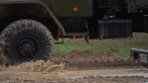 Slow motion close-up shot of spinning wheels of a military trucks Footage