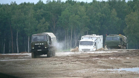Slow motion shot of Russian KAMAZ and Ural military trucks moving through Footage