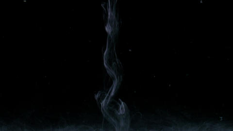 Stream of white paint poured in dark water seems a soft smoke rapidly flowing on Live Action