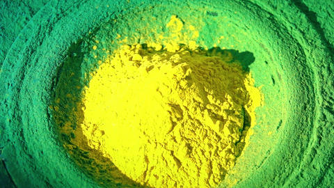 Loudspeaker throws yellow and green powder in the air, super slow motion shot Live Action