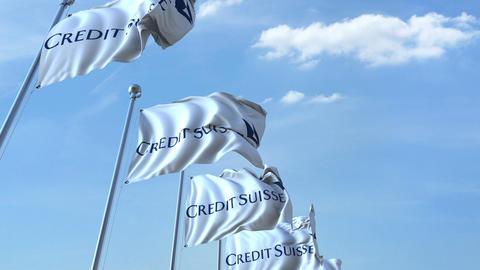 Waving flags with Credit Suisse logo against sky, seamless loop. 4K editorial Footage