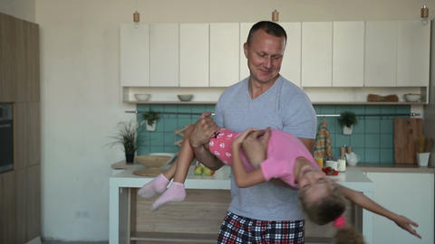 Devoted father spinning daughter in circle at home Footage