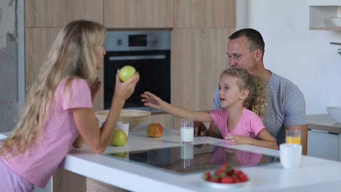 Family of three enjoying breakfast together Live Action