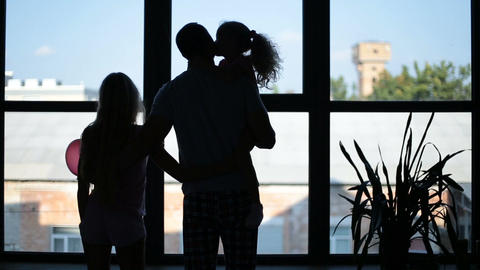 Silhouette of happy family embracing near window Footage