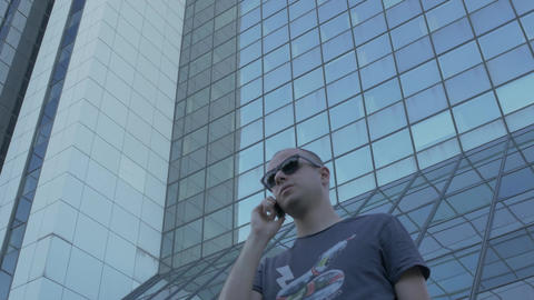 Young man talking business on the phone, negotiating, corporate skyscraper view, Footage