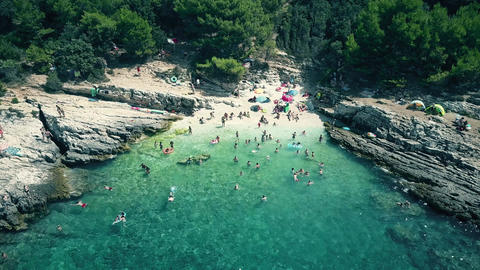 Aerial view of a small crowded rocky beach on the Adriatic sea, summer vacation Footage