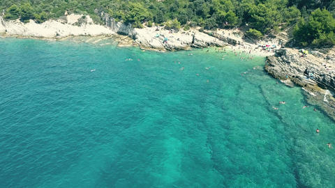 Aerial view of a small crowded rocky beach on the Adriatic sea. Summer vacation Footage