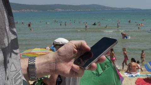Man with smartphone on the beach at seaside closeup Live Action