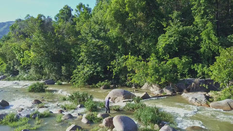 Drone Shows Man Crossing River Streaming under Sunshine Live Action