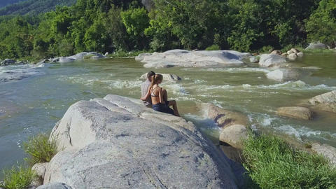 Couple Sit on Stone Hug Watch River against Jungle Footage