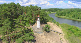White lighthouse on the top of the hill above the calm lake at sunny summer day Footage