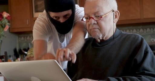Cyber thief hacking into a man's computer while he is logged in stealing data Live Action
