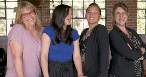Diverse multi-ethnic all female entrepreneur team smiling for the camera in a Live Action