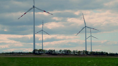 Spinning wind turbines in Austria as seen from moving car Footage