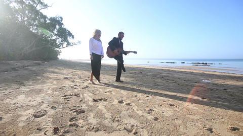 blonde guitarist plays on beach blonde girl flirts at dawn Footage