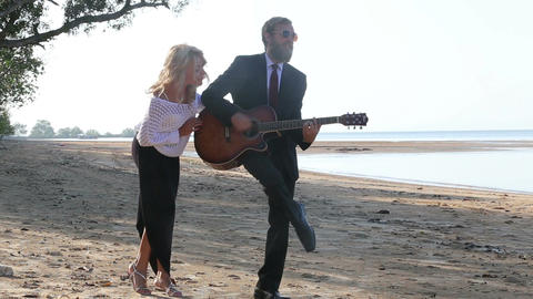 Blonde Guitarist Plays for Blonde Woman on Beach Footage