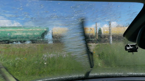 Rain on the windshield of the car. View from inside the cabin. The train goes by Footage