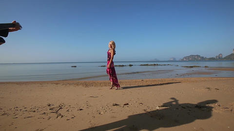 sad girl in red walks along beach guitarist's shadow approaches Footage