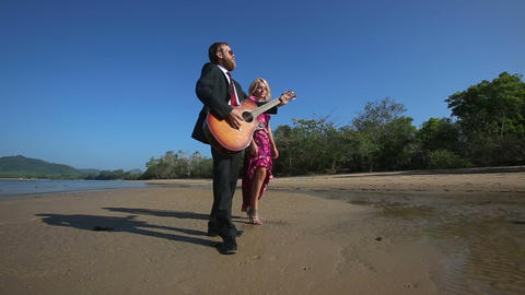 guitarist plays and blonde girl flirts posing in low tide Footage