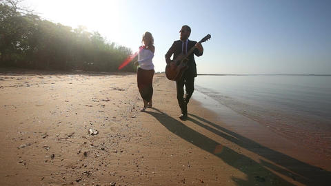 guitarist plays and blonde girl dances walking along beach Footage
