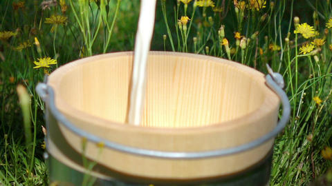 Video of pouring milk into wooden bucket-real slow motion Filmmaterial