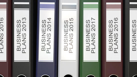 Multiple office folders with Business plans text labels different years Footage